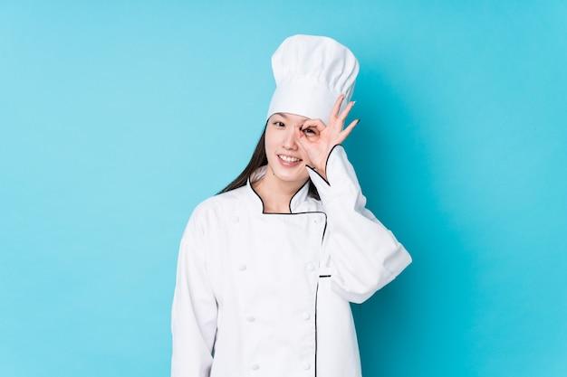 La giovane donna cinese del cuoco unico ha isolato eccitato mantenendo il gesto giusto sull'occhio.