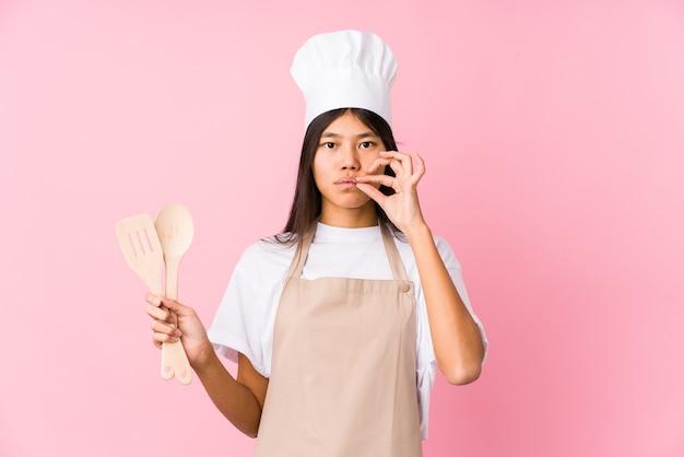 Giovane donna cinese del cuoco unico isolata con le dita sulle labbra che mantengono un segreto.
