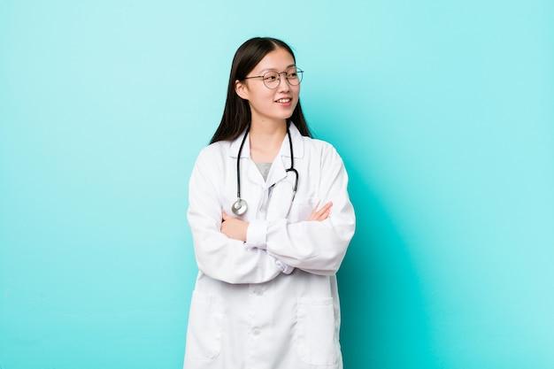 Giovane donna cinese medico sorridente fiducioso con le braccia incrociate.