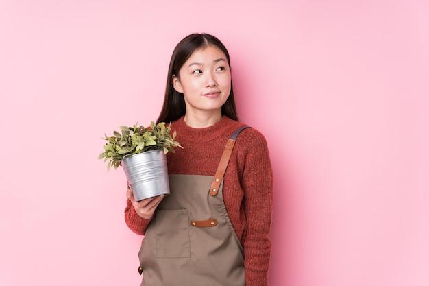 Giovane donna cinese giardiniere che tiene una pianta isolata sognando di raggiungere obiettivi e scopi