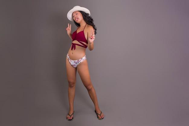 Giovane ragazza cinese in bikini e cappello che tira fuori la lingua con un'espressione divertente e beffarda