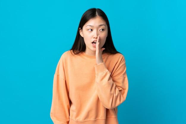 Giovane ragazza cinese sopra l'azzurro che bisbiglia qualcosa con il gesto di sorpresa mentre guarda al lato