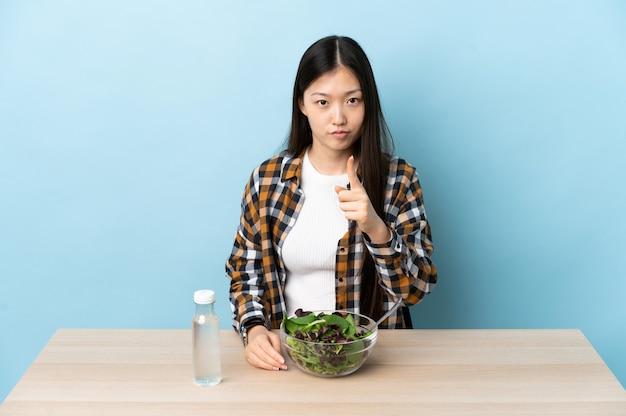 Giovane ragazza cinese che mangia un'insalata frustrata e indicando la parte anteriore