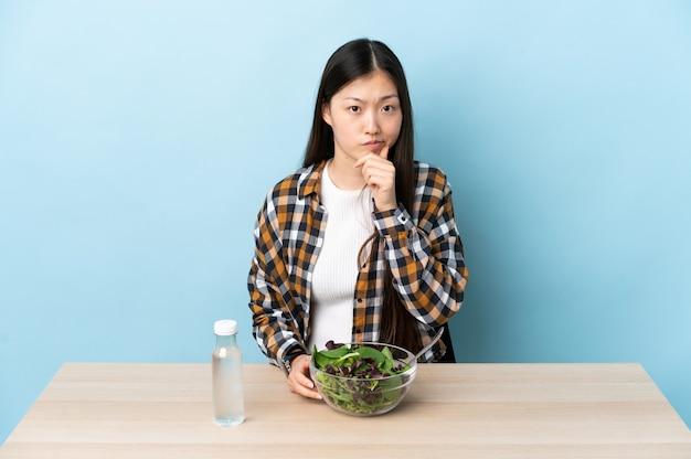 Giovane ragazza cinese che mangia un'insalata che ha dubbi e che pensa
