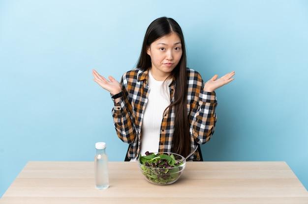 Giovane ragazza cinese che mangia un'insalata che ha dubbi mentre solleva le mani