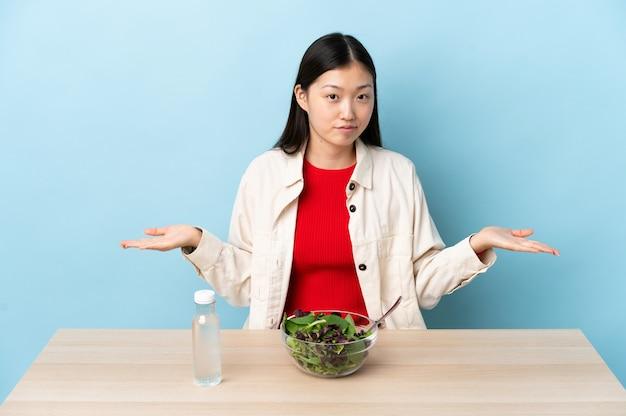 Giovane ragazza cinese che mangia un'insalata che ha dubbi