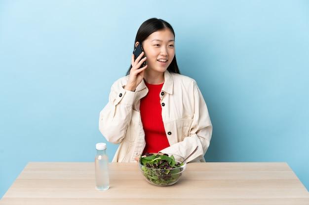 Giovane ragazza cinese che mangia un'insalata mantenendo una conversazione con il telefono cellulare
