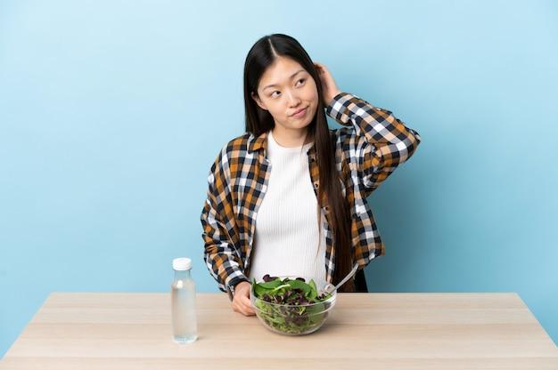 Giovane ragazza cinese che mangia un'insalata che pensa un'idea