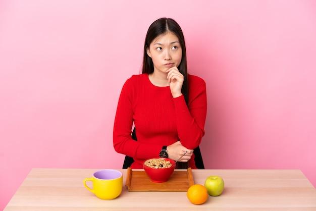 Giovane ragazza cinese che mangia prima colazione in una tabella che ha dubbi e che pensa