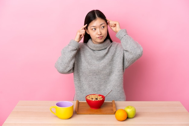 Giovane ragazza cinese che fa colazione in una tabella che ha dubbi e che pensa