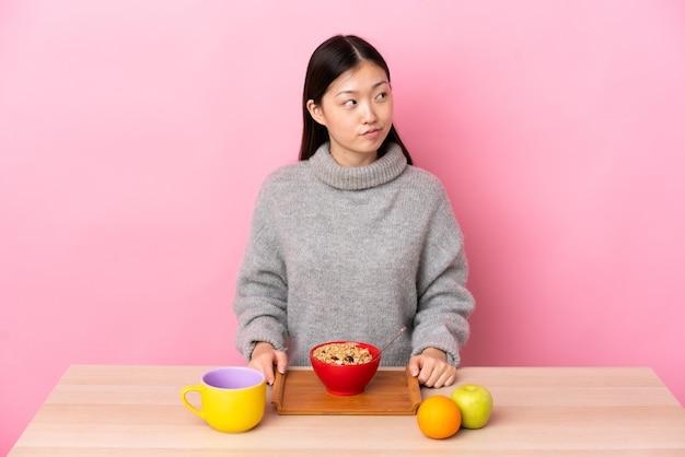 Giovane ragazza cinese che mangia prima colazione in una tabella che ha dubbi mentre guarda lato