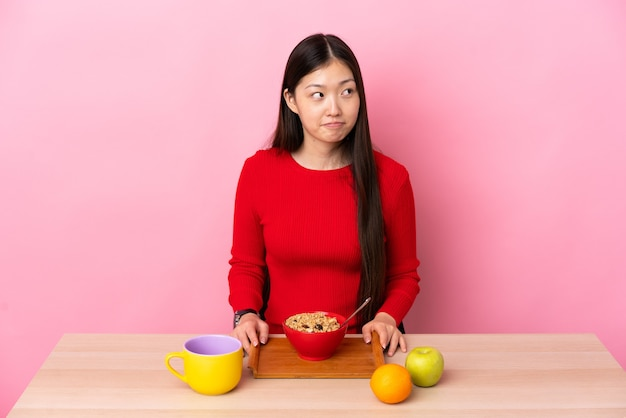 Giovane ragazza cinese che mangia prima colazione in una tabella che ha dubbi mentre osserva in su