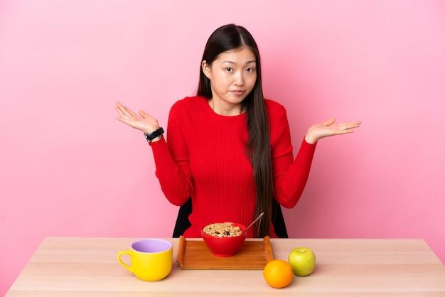 Giovane ragazza cinese che mangia prima colazione in una tabella che ha dubbi mentre solleva le mani