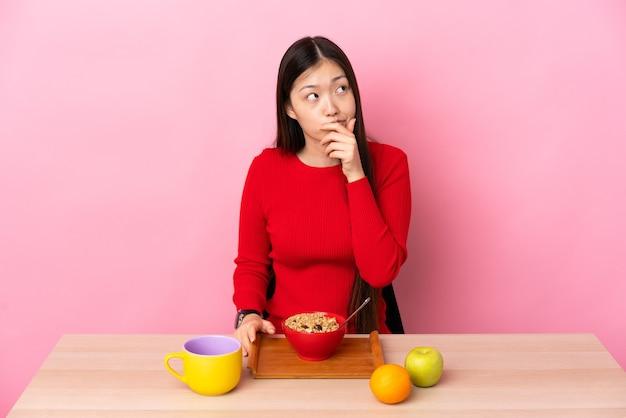 Giovane ragazza cinese che mangia prima colazione in una tabella che ha dubbi