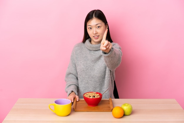 Giovane ragazza cinese facendo colazione in una tabella che mostra e alzando un dito