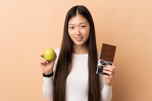 La giovane ragazza cinese ha isolato lo sfondo prendendo una tavoletta di cioccolato e una mela