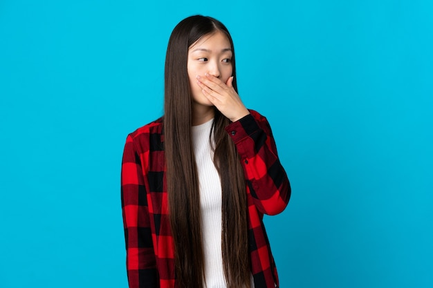Giovane ragazza cinese sul blu isolato che fa il gesto di sorpresa mentre guarda al lato