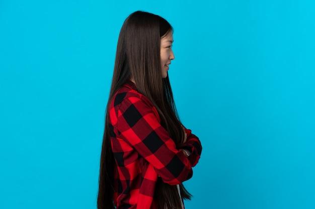 Giovane ragazza cinese sopra la parete blu isolata in posizione laterale
