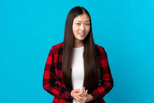 Giovane ragazza cinese sopra la risata blu isolata della parete
