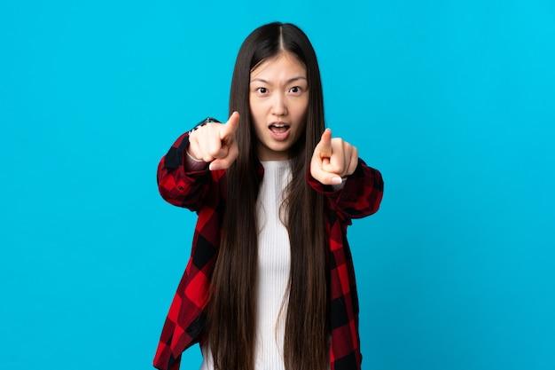 Giovane ragazza cinese sopra la parete blu isolata sorpresa e che indica la parte anteriore