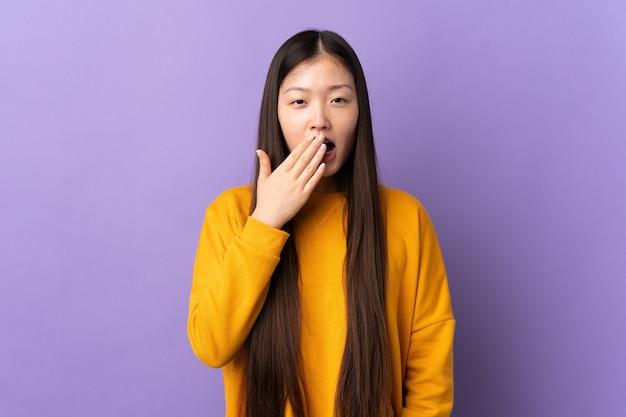 Giovane ragazza cinese su sfondo viola isolato che sbadiglia e copre la bocca spalancata con la mano
