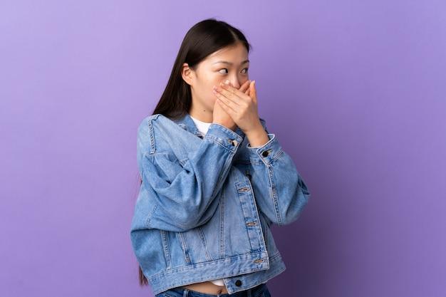 Giovane ragazza cinese sopra la bocca viola isolata della copertura e guardare al lato