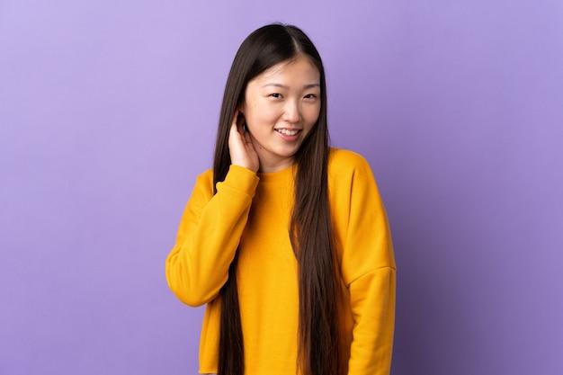 Giovane ragazza cinese sopra la risata viola isolata