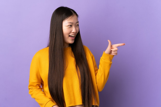 Giovane ragazza cinese sopra il dito puntato viola isolato al lato e che presenta un prodotto