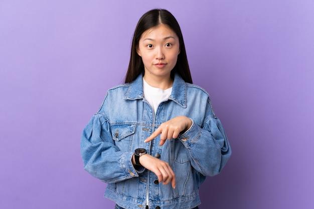 Giovane ragazza cinese sopra la parete viola isolata che fa il gesto di essere in ritardo
