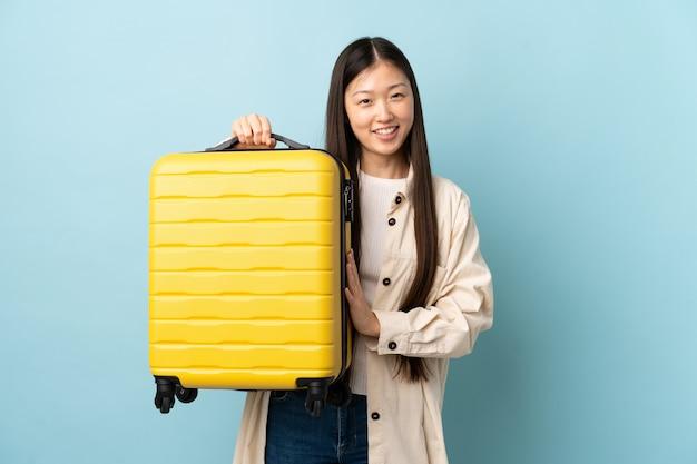 Giovane ragazza cinese sopra la parete isolata in vacanza con la valigia di viaggio