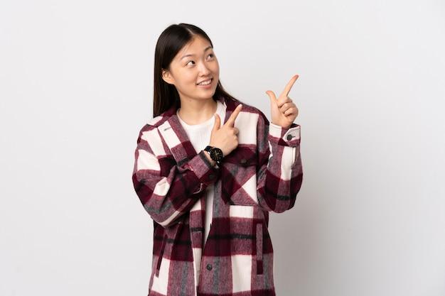 Giovane ragazza cinese su bianco isolato che punta con il dito indice una grande idea