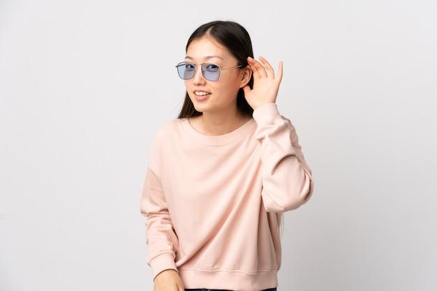 Giovane ragazza cinese sopra la parete bianca isolata che ascolta qualcosa mettendo la mano sull'orecchio