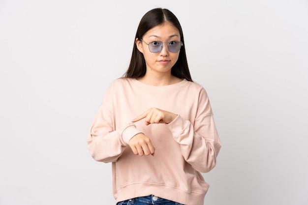 Giovane ragazza cinese sopra la parete bianca isolata che fa il gesto di essere in ritardo