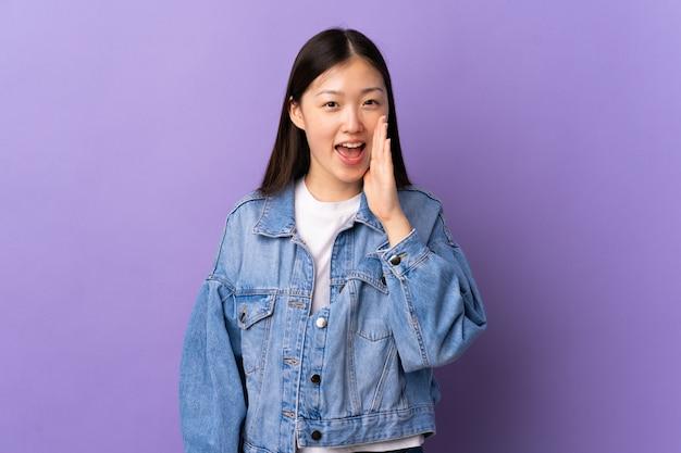 Giovane ragazza cinese sopra la parete viola che grida con la bocca spalancata