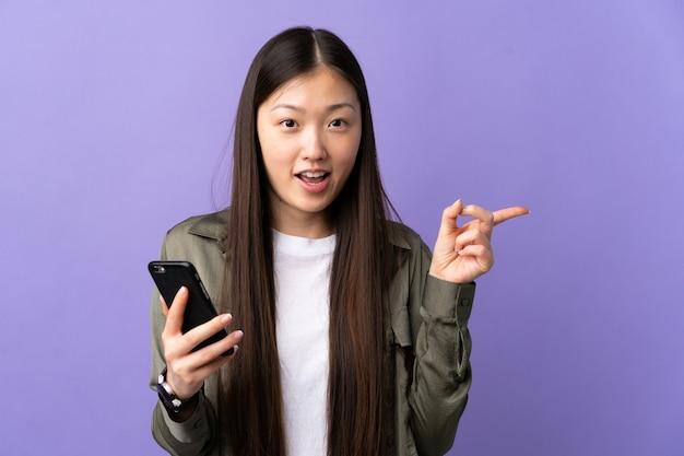 Giovane ragazza cinese utilizzando il telefono cellulare sopra isolato viola sorpreso e puntare il dito a lato