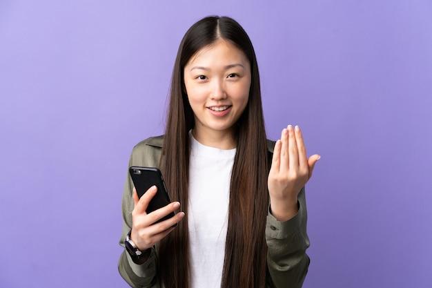 Giovane ragazza cinese che utilizza il telefono cellulare sopra la parete viola isolata che invita a venire con la mano.