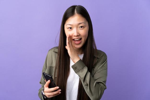 Giovane ragazza cinese che per mezzo del telefono cellulare sopra la parete porpora isolata che bisbiglia qualcosa