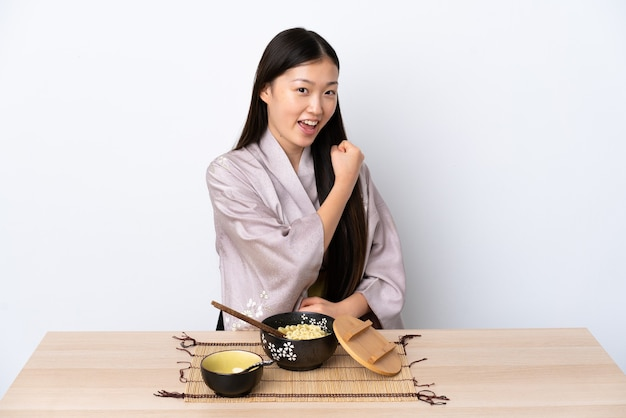 Giovane ragazza cinese che indossa il kimono e mangia le tagliatelle per celebrare una vittoria