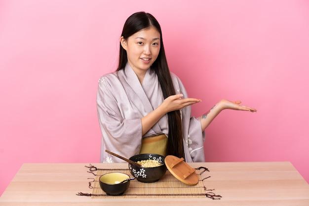 Giovane ragazza cinese che indossa il kimono e mangia le tagliatelle che allungano le mani di lato per invitare a venire