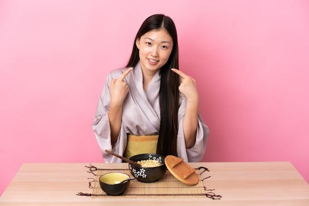 Giovane ragazza cinese che indossa il kimono e mangiare le tagliatelle dando un pollice in alto gesto