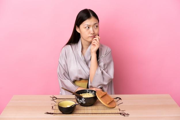 Giovane ragazza cinese che indossa il kimono e mangia le tagliatelle avendo dubbi e pensando