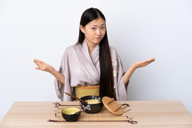 Giovane ragazza cinese che indossa il kimono e mangia le tagliatelle che hanno dubbi