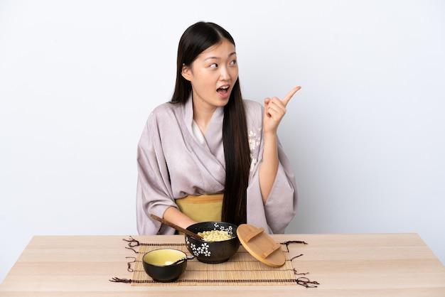 Giovane ragazza cinese che indossa il kimono e mangiare le tagliatelle che intendono