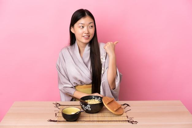 Giovane ragazza cinese che indossa il kimono e mangia le tagliatelle che punta al lato per presentare un prodotto