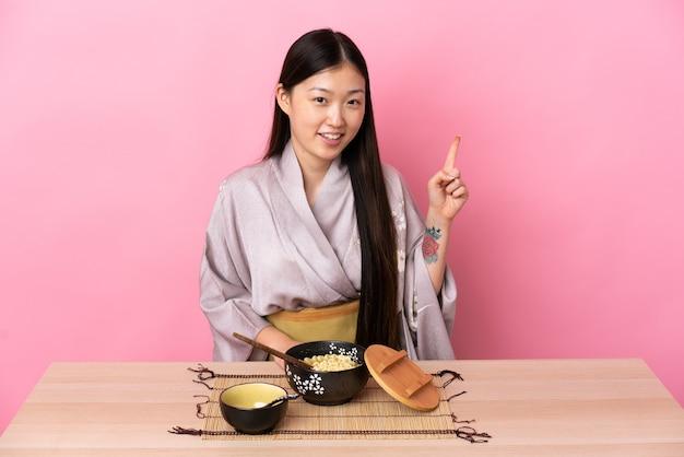 Giovane ragazza cinese che indossa il kimono e mangia le tagliatelle mostrando e alzando un dito in segno del meglio