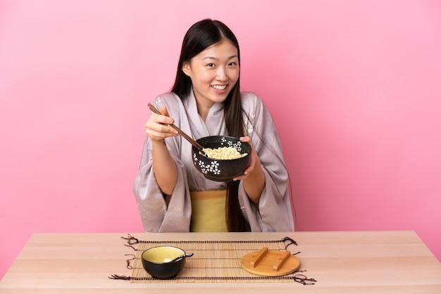Giovane ragazza cinese che indossa il kimono e mangiare le tagliatelle in un tavolo in rosa