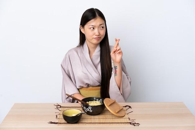 Kimono da portare della giovane ragazza cinese e mangiare le tagliatelle con le dita che attraversano e che desiderano il meglio