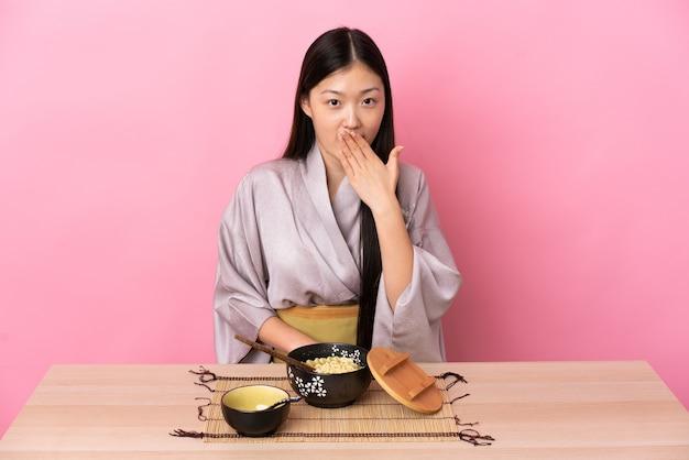 Giovane ragazza cinese che indossa il kimono e mangiare spaghetti