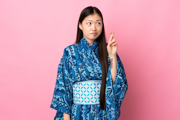 Giovane ragazza cinese che indossa un kimono sopra la parete isolata con le dita incrociate e che desiderano il meglio