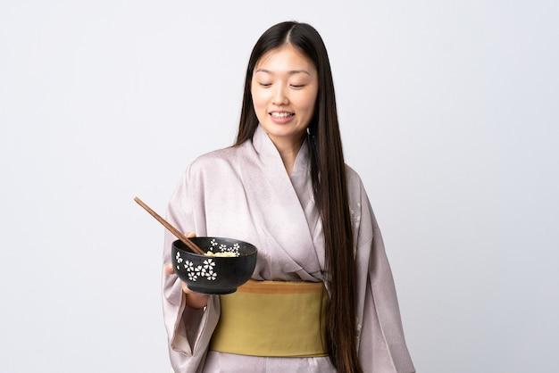 Giovane ragazza cinese che indossa un kimono isolato su sfondo bianco con felice espressione mentre si tiene una ciotola di spaghetti con le bacchette